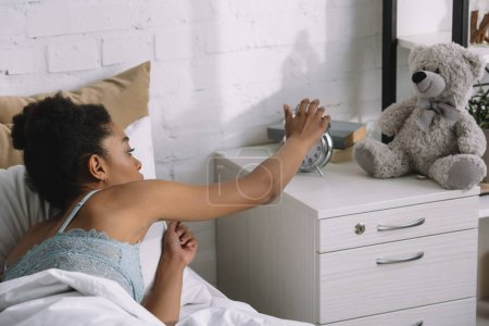 african american girl waking up and turning off alarm clock in bedroom