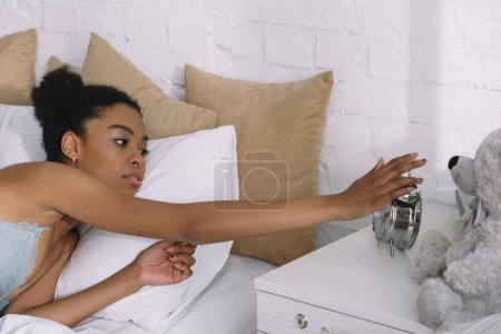 beautiful african american girl waking up and turning off alarm clock in bed