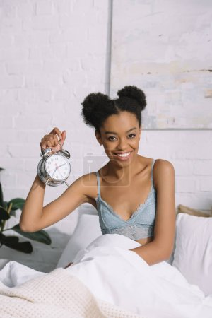 smiling african american girl holding alarm clock while sitting in bed in morning
