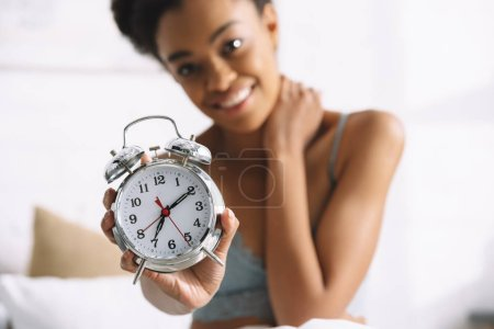 selective focus of afro girl showing alarm clock in morning