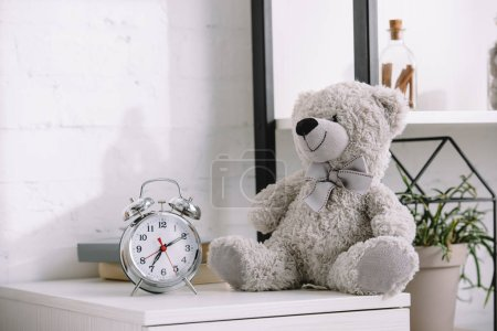 alarm clock and grey teddy bear on nightstand