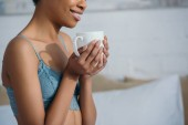 cropped view of smiling african american girl holding cup of coffee