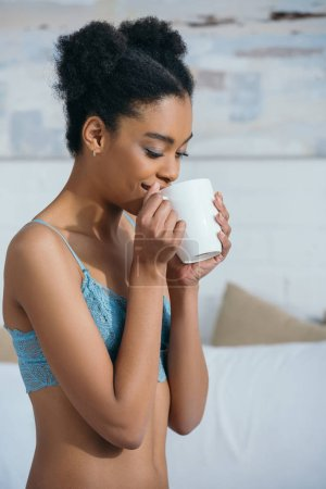happy african american girl drinking coffee in bedroom in morning