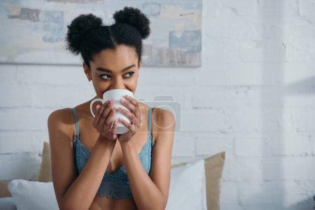 attractive smiling afro girl drinking coffee