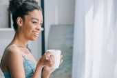attractive smiling african american girl with cup of coffee looking at window in the morning