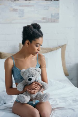 beautiful african american girl with teddy bear sitting on bed in morning