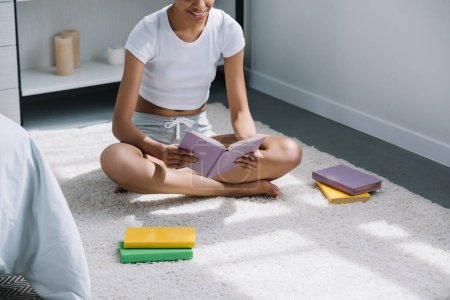 cropped view of african american student reading book on floor in bedroom