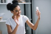 happy young woman making video call with smartphone at home