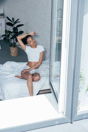 Photo pour Séduisante jeune femme assise sur le lit dans la matinée à la maison - image libre de droit