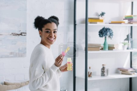 side view of happy young woman with soap bubbles at home