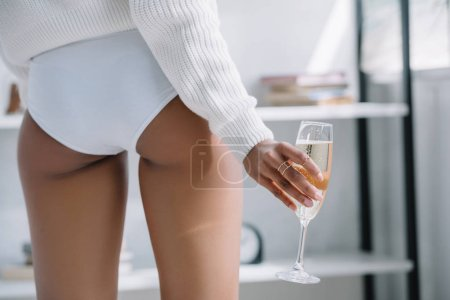 cropped shot of woman in underwear holding glass of champagne at home