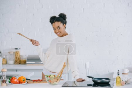 happy young woman preparing breakfast at kitchen and looking at camera