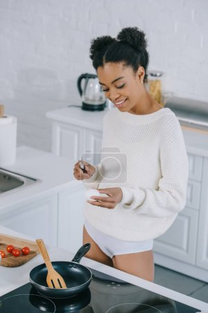 smiling young woman preparing scrambled egg for breakfast at kitchen