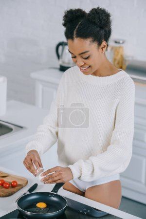 happy young woman frying scrambled egg for breakfast at kitchen