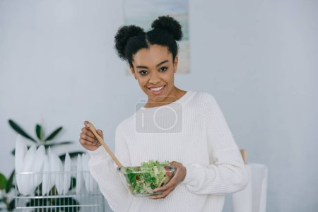 happy young woman with bowl of healthy salad at kitchen