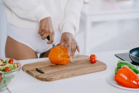 cropped shot of woman slicing vegetables for breakfast at kitchen