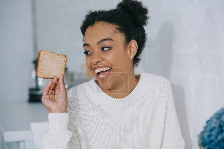 happy young woman with slice of bread at home