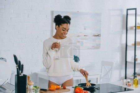 Photo pour Belle jeune femme avec verre de champagne préparer le petit déjeuner à la maison - image libre de droit