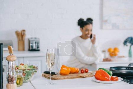Photo pour Floue souriante jeune femme parlant par téléphone avec des légumes et coupe de champagne au premier plan à la maison - image libre de droit