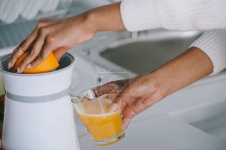 cropped shot of woman squeezing fresh orange juice at kitchen