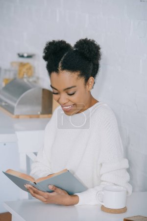 happy young woman reading book during coffee break at home