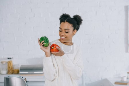 beautiful young woman with ripe bell peppers at kitchen