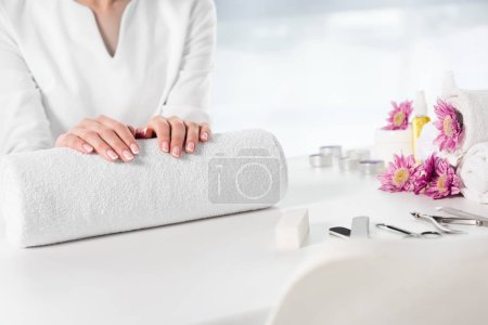 cropped image of woman holding hands at table with towels, flowers, candles, aroma oil bottles and instruments for manicure in beauty salon