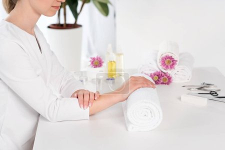 Photo for Cropped shot of woman holding hands at table with towels, flowers, candles, aroma oil bottles and instruments for manicure in beauty salon - Royalty Free Image