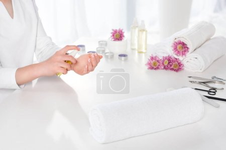 Photo for Cropped image of woman using aroma oil at table with towels, flowers, candles and instruments for manicure in beauty salon - Royalty Free Image