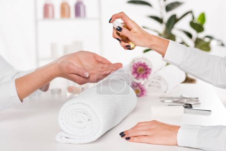 cropped shot of manicurist spraying aroma oil on hands of woman at table with flowers and towels in beauty salon