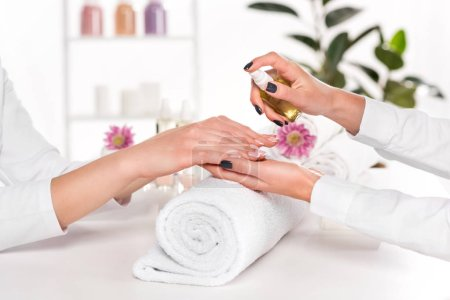 partial view of manicurist spraying aroma oil on hands of woman at table with flowers and towels in beauty salon