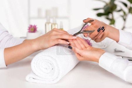 cropped image of woman receiving manicure by beautician with nail clippers at table with flowers and towels in beauty salon
