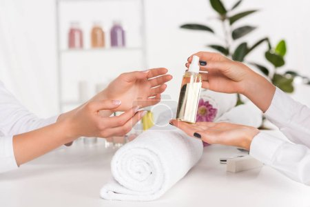 cropped image of manicurist showing aroma oil bottle to woman sitting at table in beauty salon