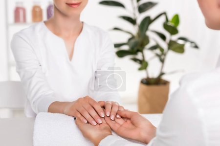 cropped image of manicurist looking at hands of woman at table in beauty salon