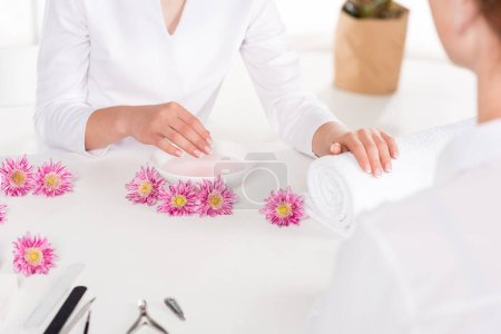 partial view of manicurist and woman receiving bath for nails at table with flowers, nail clippers, nail files and cuticle pusher in beauty salon