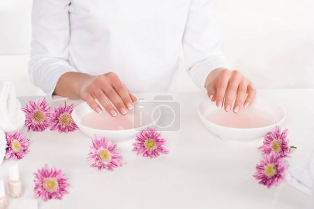 partial view of woman receiving bath for nails at table with flowers, towels and nail polishes in beauty salon