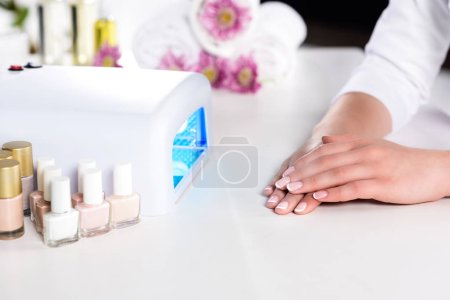cropped image of woman holding hand near working uv lamp at table with flowers, nails polishes and towels in beauty salon