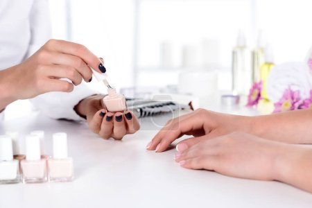cropped shot of woman receiving manicure by beautician with nail polish at table with flowers and towel in beauty salon