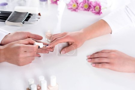partial view of woman receiving manicure by beautician with nail polish at table with flowers and towel in beauty salon