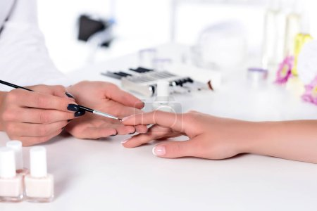 partial view of beautician doing manicure to woman at table with nail polishes in beauty salon