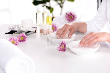 cropped image of woman receiving bath for nails at table with flowers, towels, candles, aroma oil bottles, nail polishes, cream container and tools for manicure in beauty salon
