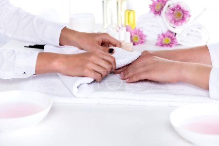 partial view of manicurist drying hands of woman after bath for nails in beauty salon