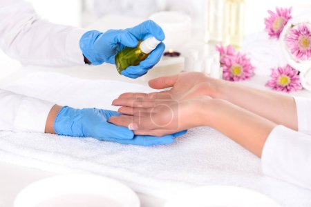 cropped image of manicurist in latex gloves spraying aroma oil on hands of woman in beauty salon