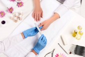 elevated view of beautician in latex gloves doing manicure to woman by nail file at table with flowers, towels, nail clippers, candles, nail polishes, aroma oil bottles and cuticle pusher