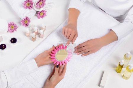 Photo pour Vue de dessus de manucure détenant des échantillons de vernis à ongles tout en pointant de doigt à table avec des bouteilles d'huile de parfum, des bougies, des serviettes, des fleurs et des vernis à ongles dans un salon de beauté de femme - image libre de droit