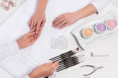 Photo pour Recadrée tir d'esthéticienne fait manucure pour femme à table de sel de mer coloré, vernis à ongles, nail clippers et outils pour la manucure dans un salon de beauté - image libre de droit
