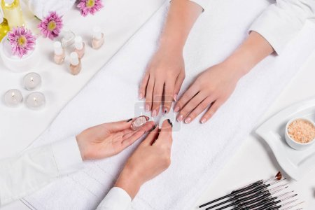 Photo for Partial view of manicurist showing nail polish to woman at table with candles, sea salt, flowers, aroma oil bottles, towels and tools for manicure - Royalty Free Image