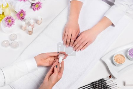 Photo for Cropped image of manicurist showing nail polish to woman at table with candles, sea salt, flowers, aroma oil bottles, towels and tools for manicure - Royalty Free Image