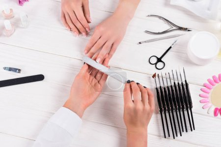 cropped image of beautician doing manicure by nail file to woman at table with cream, nail polishes, scissors, cuticle pusher, nail clippers, samples of nail varnishes