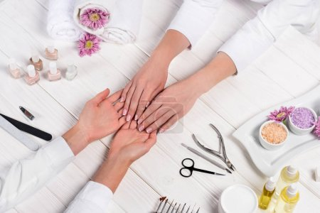 Photo for Cropped image of manicurist looking at hands of woman at table with flowers, towels, nail polishes, nail files, nail clippers, sea salt, cream, cuticle pusher, scissors and aroma oil bottles - Royalty Free Image